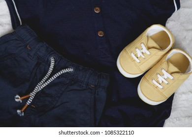 Toddler Clothes Flat Lay, yellow sneakers, dark blue pants and button up shirt