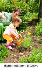Toddler daughter helping mother in the garden