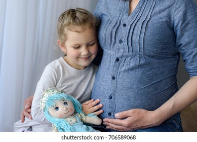 toddler daughter listening to belly pregnant mother at home