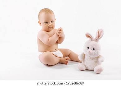 A toddler in a diaper sits next to his plush hare, on an isolated white background