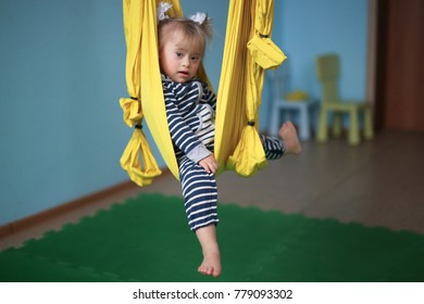 Toddler with Down syndrome antigravity yoga, yellow hammock. Lifestyle and tinting, classes at a children's center