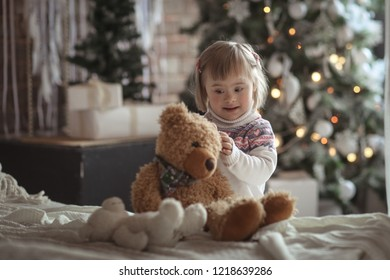 toddler with down syndrome on the christmas tree with a new years gift a teddy