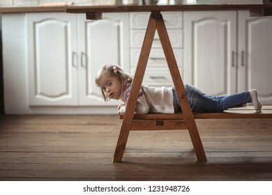 Toddler with Down syndrome in a sweater plays under the table in the kitchen