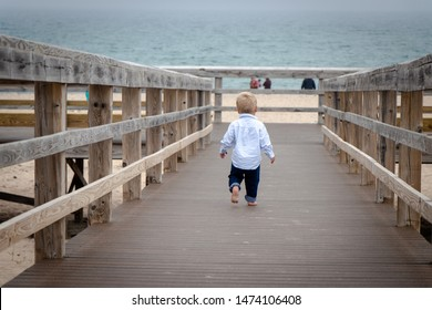 Toddler in dress shirt on boardwalk at the beach