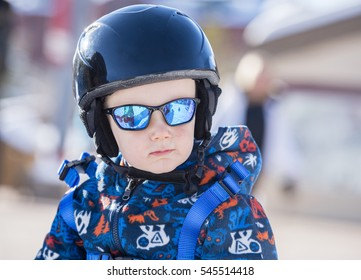 Toddler Dressed Safely for Skiing with Helmet, Harness & Sunglasses