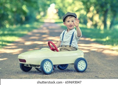 Toddler driving a retro car, funny boy in toy car