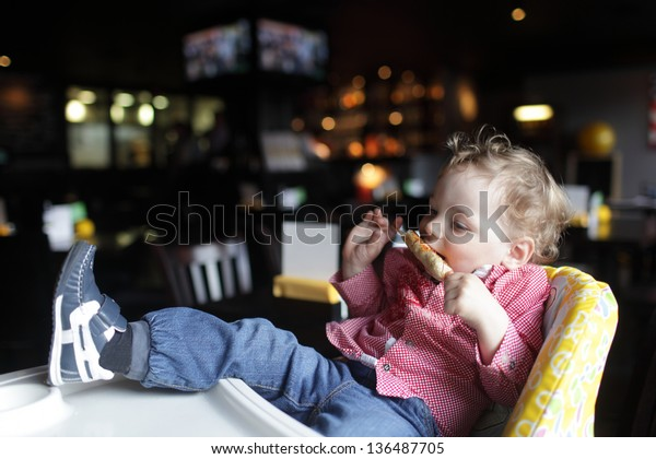Toddler is eating kebab in a high chair at a restaurant