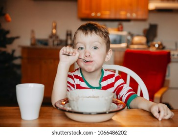 Toddler eating porridge messy. baby eats with a spoon himself