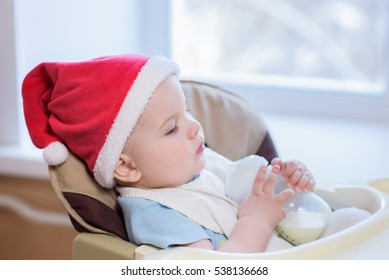 toddler eats at the table in a Christmas hat