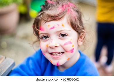 Toddler enjoying messy play at preschool nursery playgroup