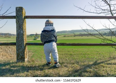 Toddler enjoying view into rural countryside in srping with tractor approching.