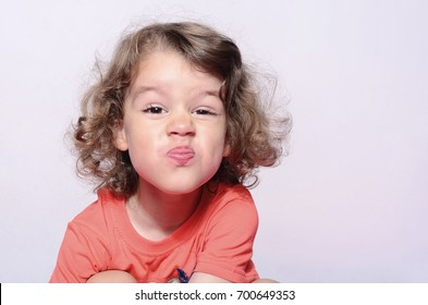 Toddler expressions, beautiful boy emotions, kid having fun, boy's kiss. Kid making funny faces. Boy with long curly hair.