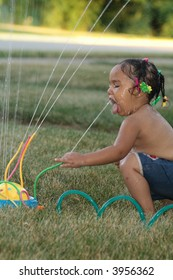 A toddler getting a drink from her sprinkler