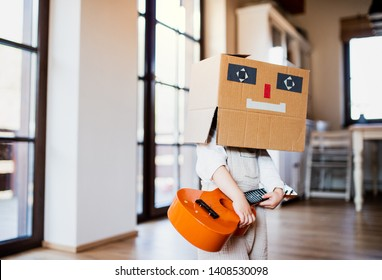 A toddler girl with carboard monster on head playing indoors at home.