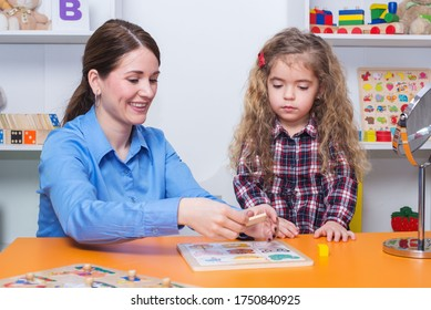 Toddler girl in child occupational therapy session doing sensory playful exercises with her therapist.