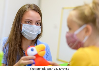 Toddler girl in child occupational therapy session doing playful exercises with her therapist during Covid - 19 pandemic, both wearing protective face masks.