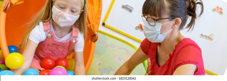 Toddler girl in child occupational therapy session doing playful exercises with her therapist during Covid - 19 pandemic, both wearing protective face masks. Web banner.