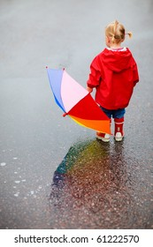 Toddler girl with colorful umbrella outdoors at rainy day
