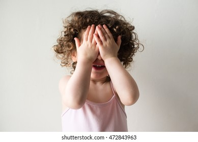 Toddler girl with curly hair with hands covering face playing peekaboo against neutral background