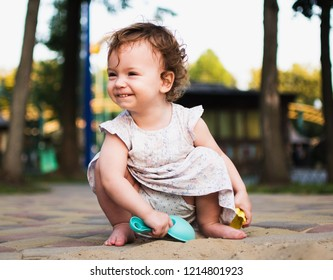 Toddler girl with curly hair plays in a sandbox with a spatula