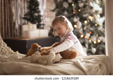 toddler girl with down syndrome plays with toy bears christmas gifts concept new year
