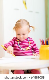 Toddler girl drawing with pencils