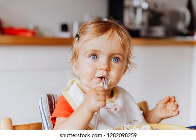 Toddler girl eating cake with a fork in kitchen  – Kempen, Germany