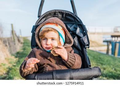 Toddler girl eating homemade wholegrain bun – Hindeloopen, Friesland, Netherlands