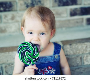 Toddler girl eating a messy lollipop sucker