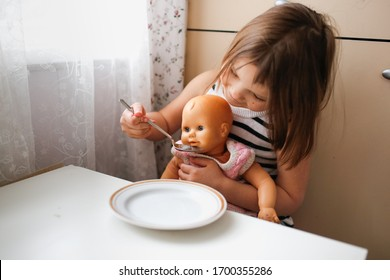Toddler girl feeds a doll with spoon at the children's table, role-playing games and daughter as a mother. Lifestyle in a real interior,