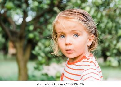 Toddler girl in garden looking at camera - Cirali, Antalya Province, Turkey