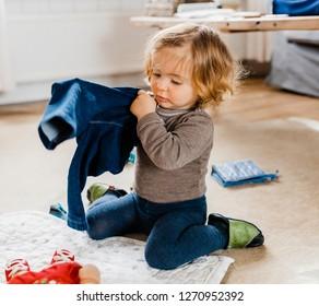 Toddler girl getting dressed in living room - Hindeloopen, Friesland, Netherlands