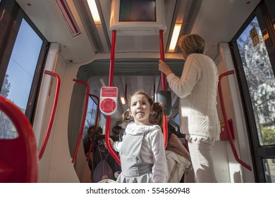 Toddler girl having fun during a ride at streetcar, Spain