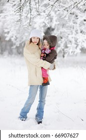Toddler girl and her mother on beautiful snowy winter day