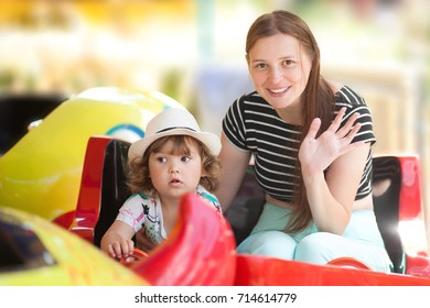 Toddler girl and her young mom together in the amusement park, lifestyle. Riding children attraction, sitting in the color wagon. Summer day.