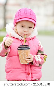 toddler girl with hot drink outdoors
