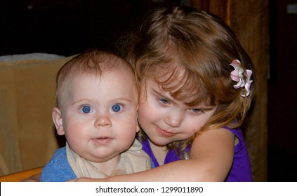 Toddler girl hugging her baby brother