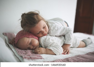 Toddler Girl Hugs a Sleeper Cute little baby in a crocheted cap on her stomach on a bed