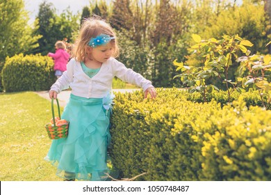 Toddler girl hunting chocolates eggs at easter, spring in gardens