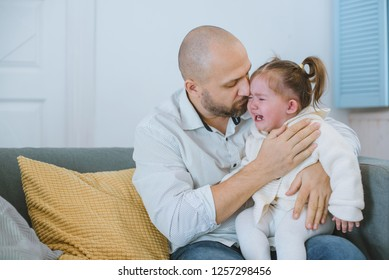 The toddler girl in a knitted blouse and with two tails cries in her father's arms, who hugs and comforts her.