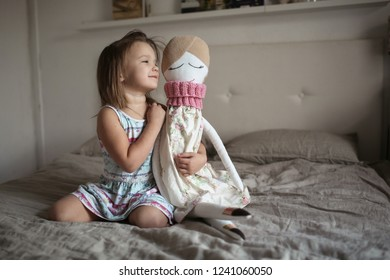 Toddler girl with a large soft handmade doll in a bright bedroom, the concept of needlework and childhood