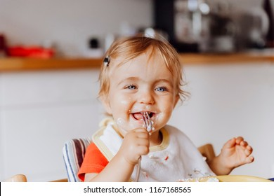 Toddler girl laughing and holding a fork in kitchen  – Kempen, Germany