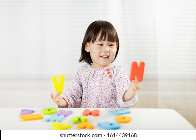 toddler girl learning alphabet letter at home against white background