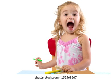 Toddler girl learning at the table very excited , her eyebrowns are raised and mouth opened large holding colorful markers