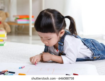 Toddler girl lying comfortable on carpet floor drawing on paper with colorful pens in the house, Educational concept for school kids