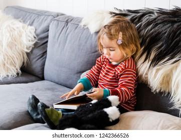 Toddler girl on sofa reading picture book - Hindeloopen, Friesland, Netherlands