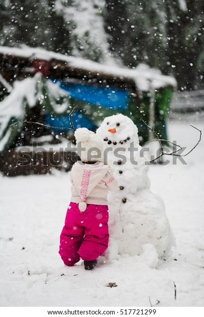 A toddler girl in a pink snowsuit with wool hat toque builds a large snowman with carrot nose and smiling face in backyard with snowflakes snow falling in winter at Christmas