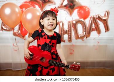 toddler girl  play ukulele celebrating her third birthday at home