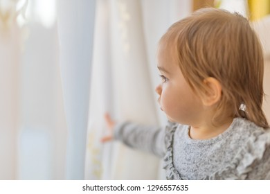 Toddler girl playing at home with the curtain and door. Cute portrait of baby girl, natural light portrait