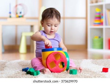 toddler girl playing indoors with sorter toy sitting on soft carpet